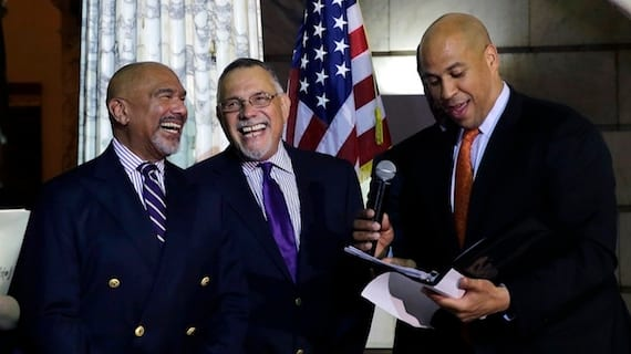 El Alcalde de Newark, Cory Booker (der.), oficiando la boda de Joseph Panessidi, 65, y su pareja Orville Bell, 65 (izq.), en la alcaldía de Newark City en la medianoche del lunes